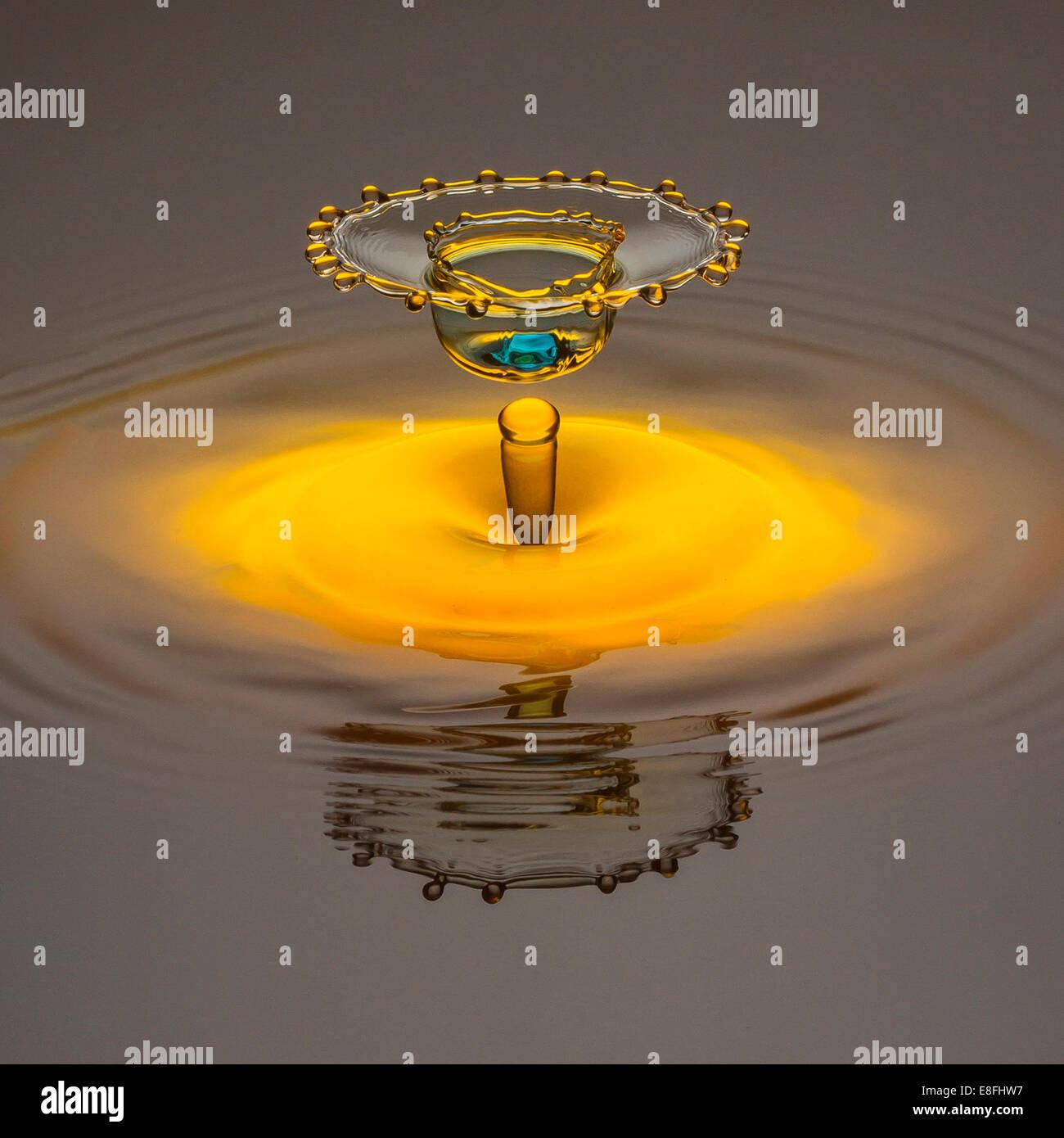 Gota de agua amarilla formando corona con luz azul dot en oriente Imagen De Stock