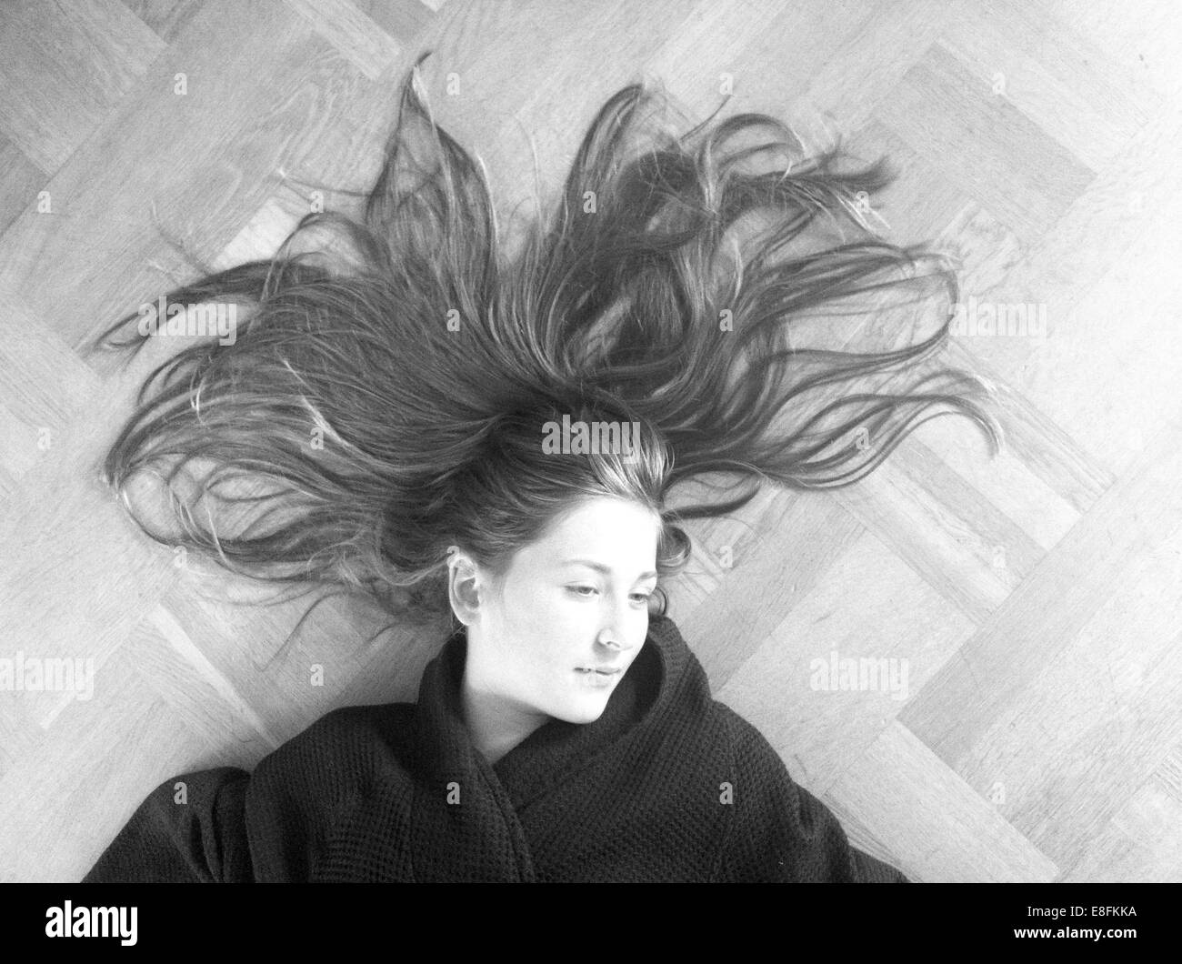 Chica recostada sobre un piso de madera con su cabello esparcido Imagen De Stock