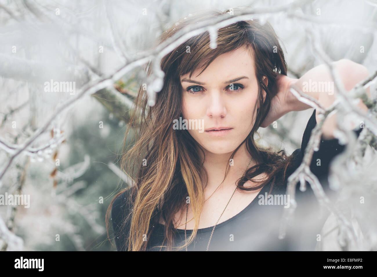Retrato de mujer joven de pie entre las ramas congeladas Imagen De Stock