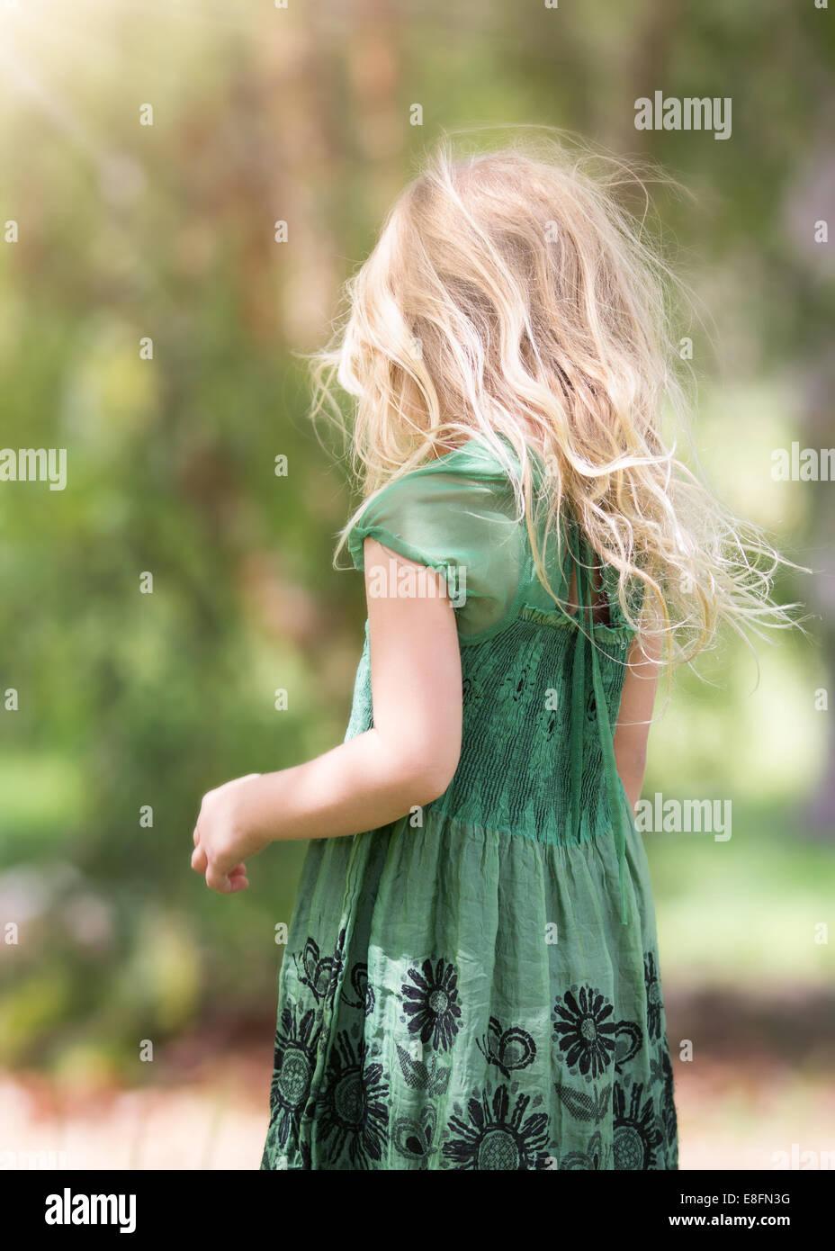 Vista trasera de la niña (4-5) vistiendo vestido verde Imagen De Stock