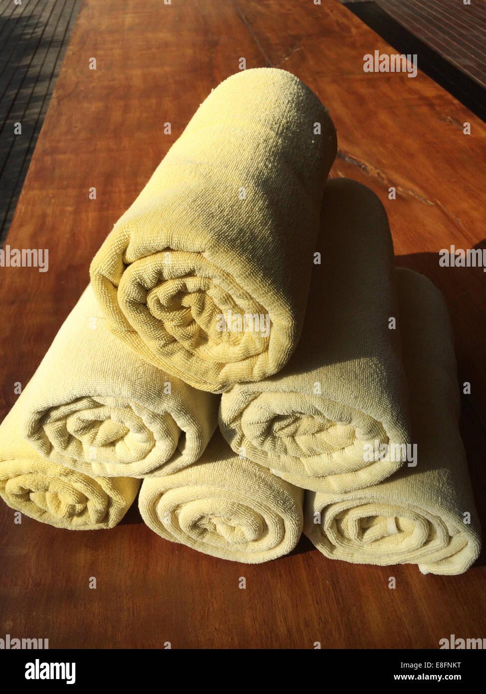 Toallas enrolladas sobre mesa de madera Foto de stock