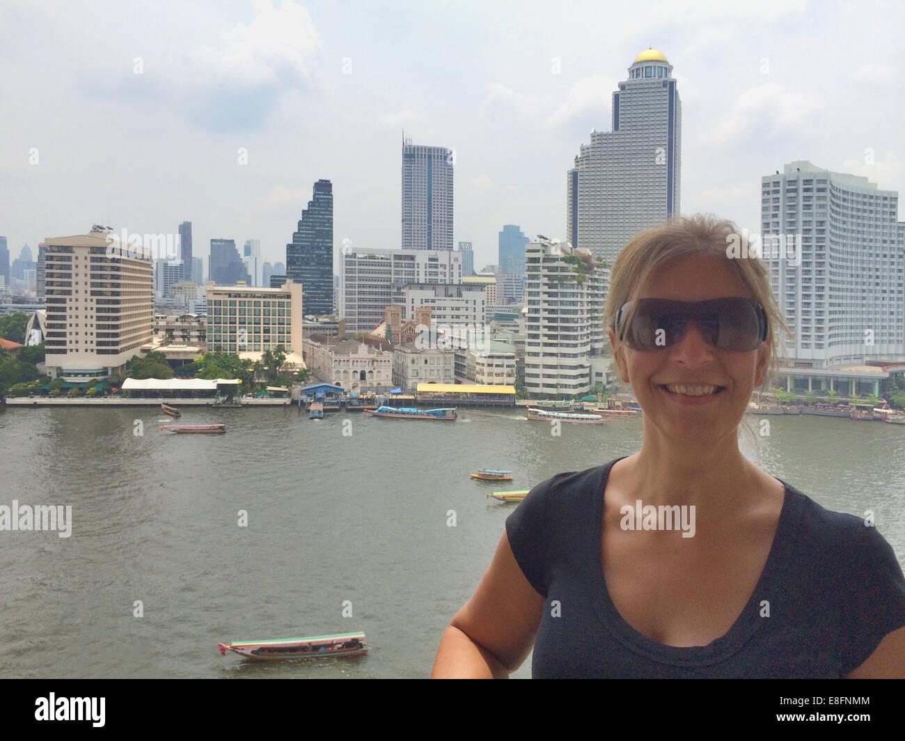 Tailandia, Bangkok, Retrato de mujer con paisaje urbano en segundo plano. Imagen De Stock