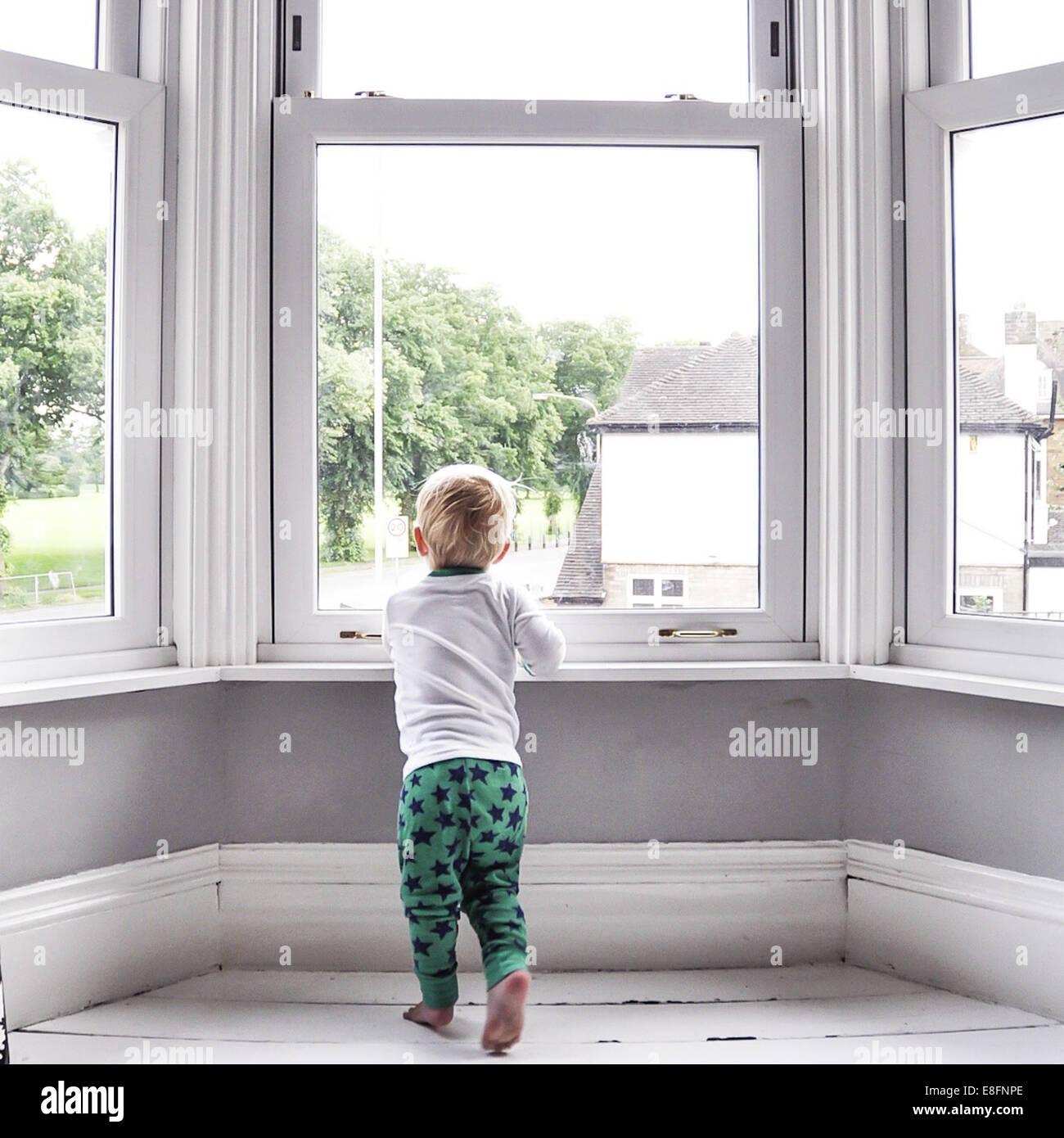 Chico mirando fuera del Salón de la ventana Imagen De Stock