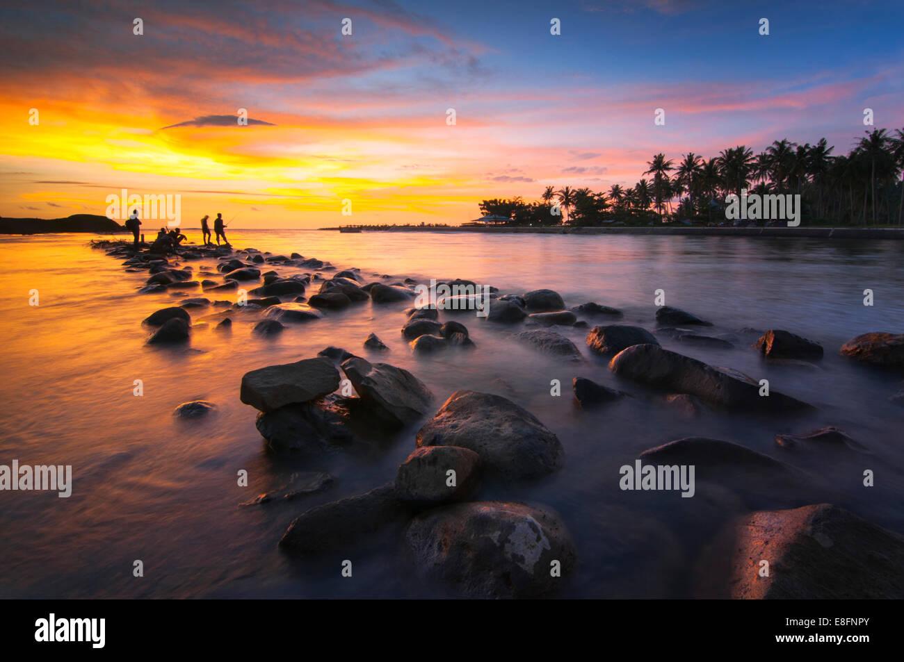 Indonesia, Sumatra, en el oeste de Sumatra, la silueta de la gente en la playa en el atardecer. Imagen De Stock