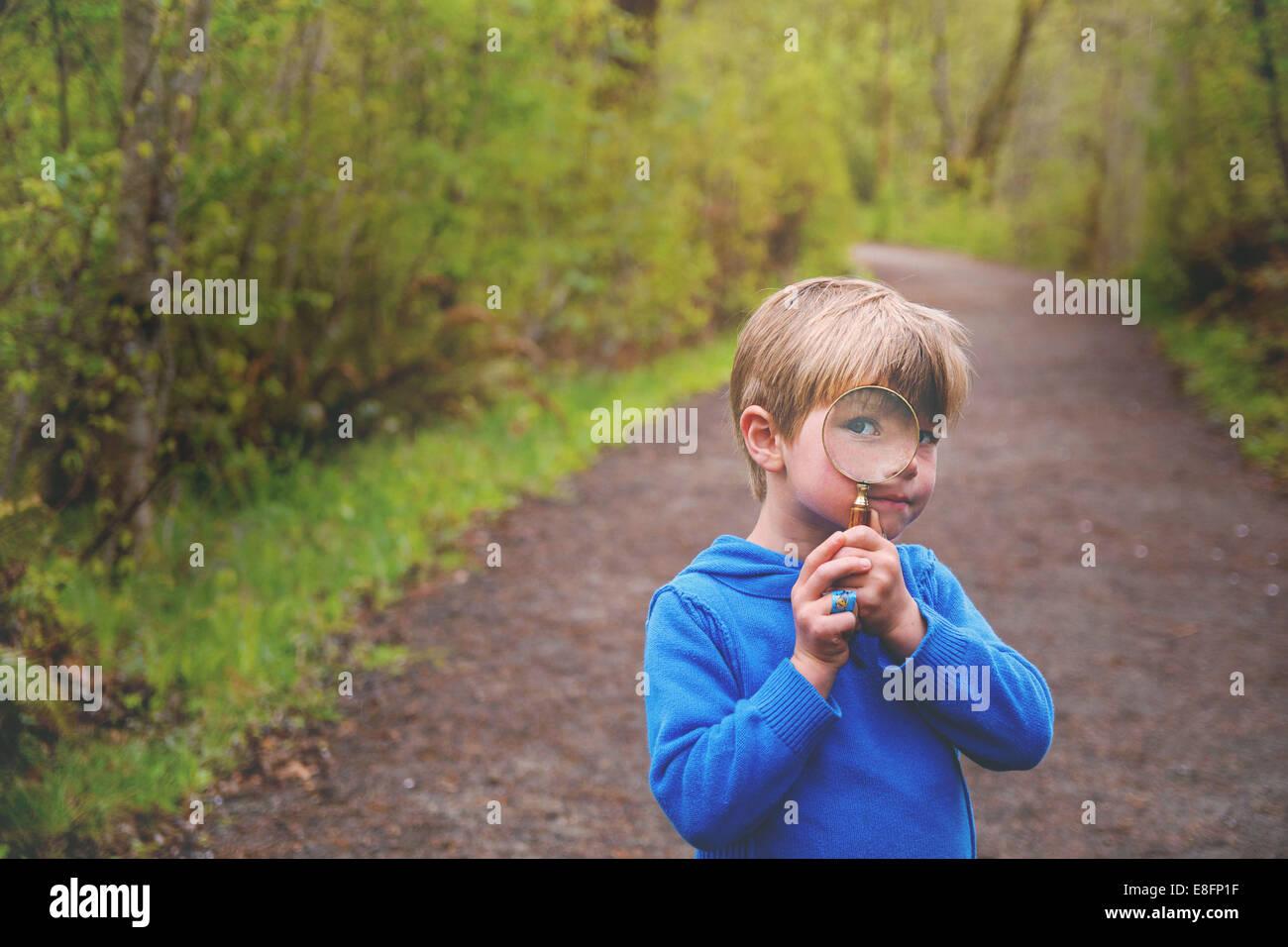 Boy (4-5) mirando a través de una lupa en Nature Trail Imagen De Stock