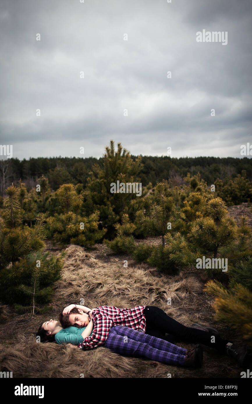 Adolescentes (14-15) tumbado en el suelo y abrazando Imagen De Stock