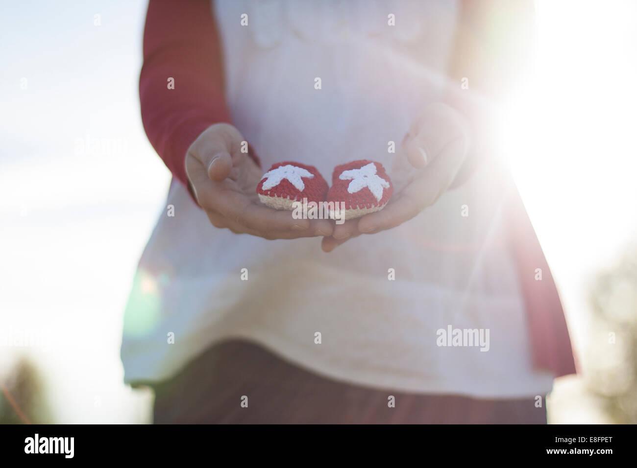 Mujer embarazada celebrar pequeñas baby shoes Imagen De Stock