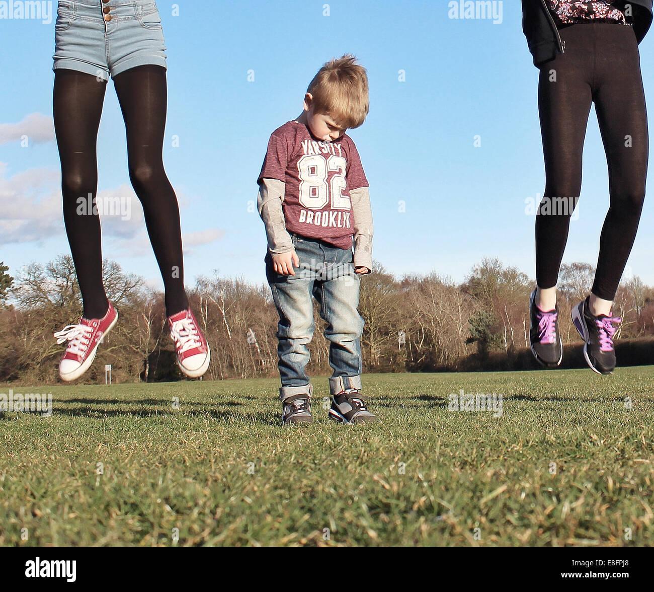 Boy refunfuñar como dos niñas saltar más alto que él puede Imagen De Stock