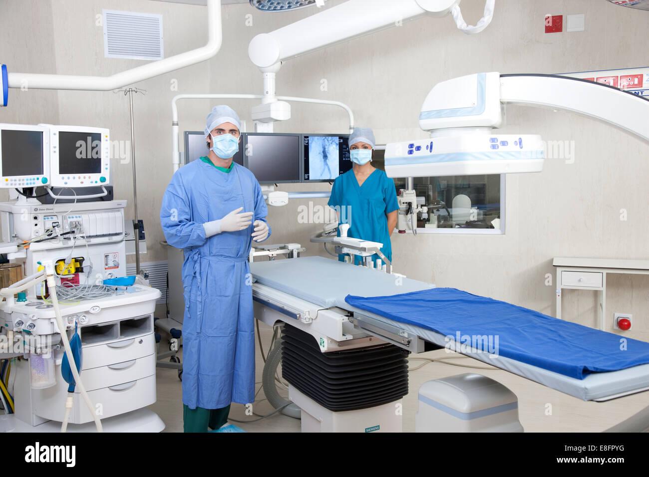 Los médicos de remolque de pie en quirofano con sistema de imágenes robóticas Foto de stock