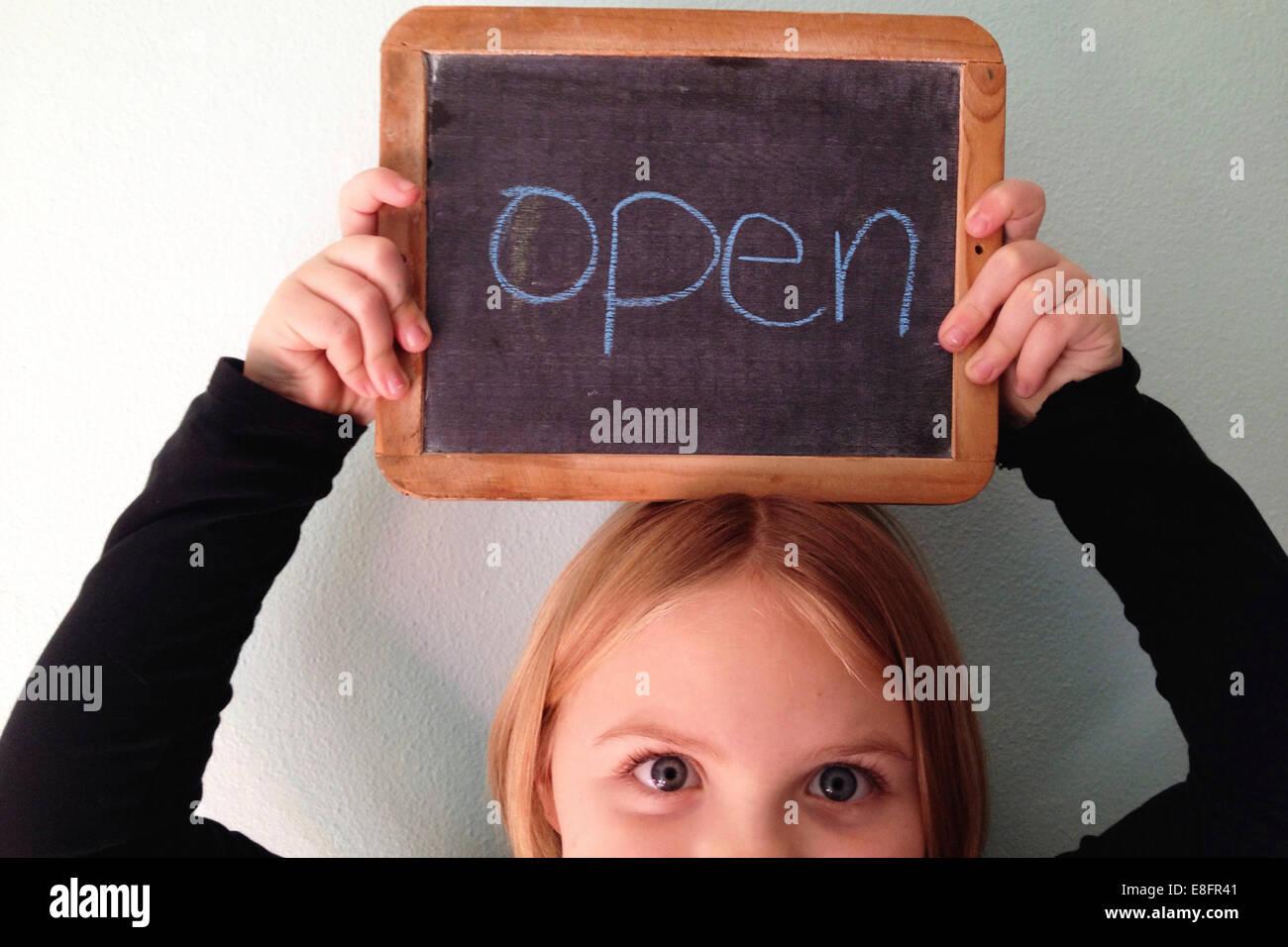 Retrato de una chica sujetando una pizarra por encima de su cabeza con la palabra open Imagen De Stock