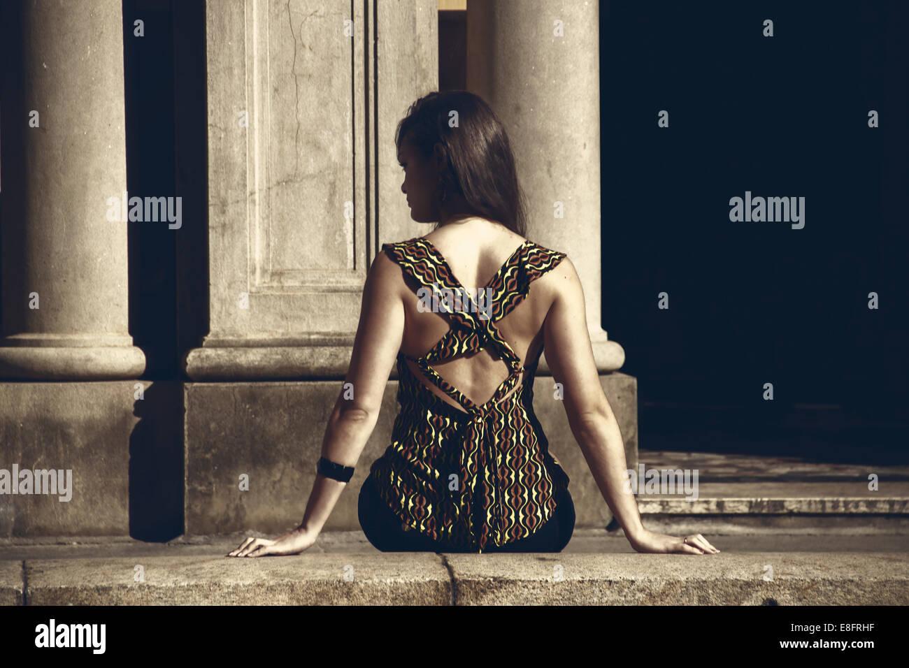 Vista trasera de una mujer sentada sobre una pared Imagen De Stock