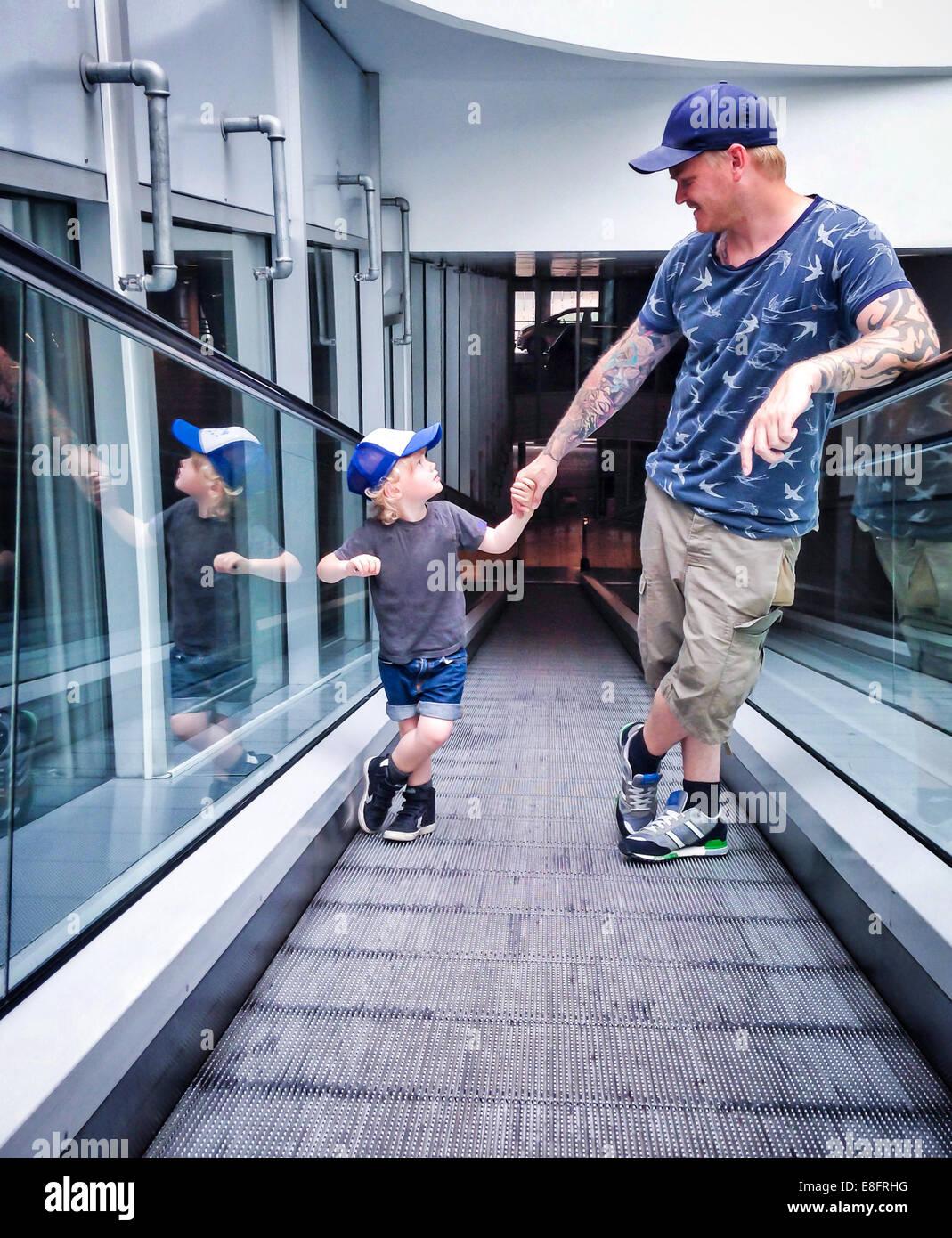 Padre e hijo de pie sobre una travelator Imagen De Stock