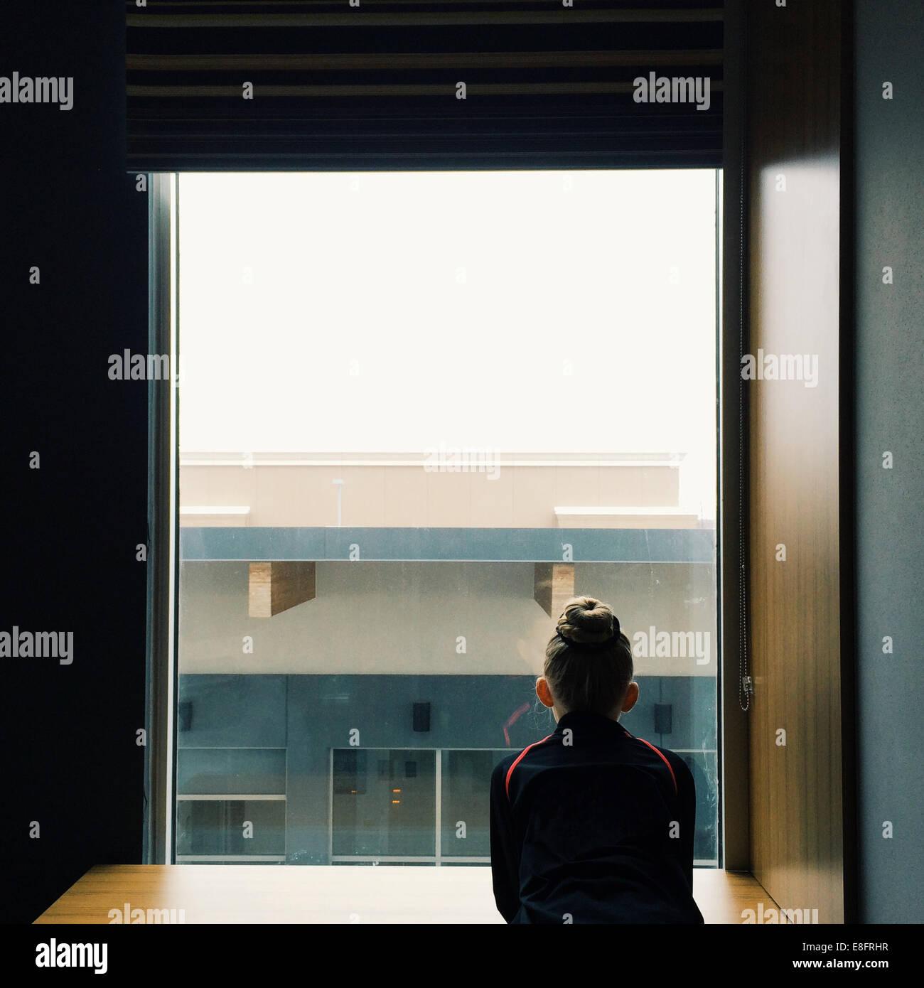 Chica (8-9) mirando hacia afuera de la ventana Imagen De Stock