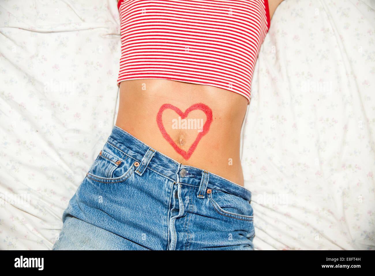 Corazón en forma de dibujo en el estómago de una mujer Foto de stock