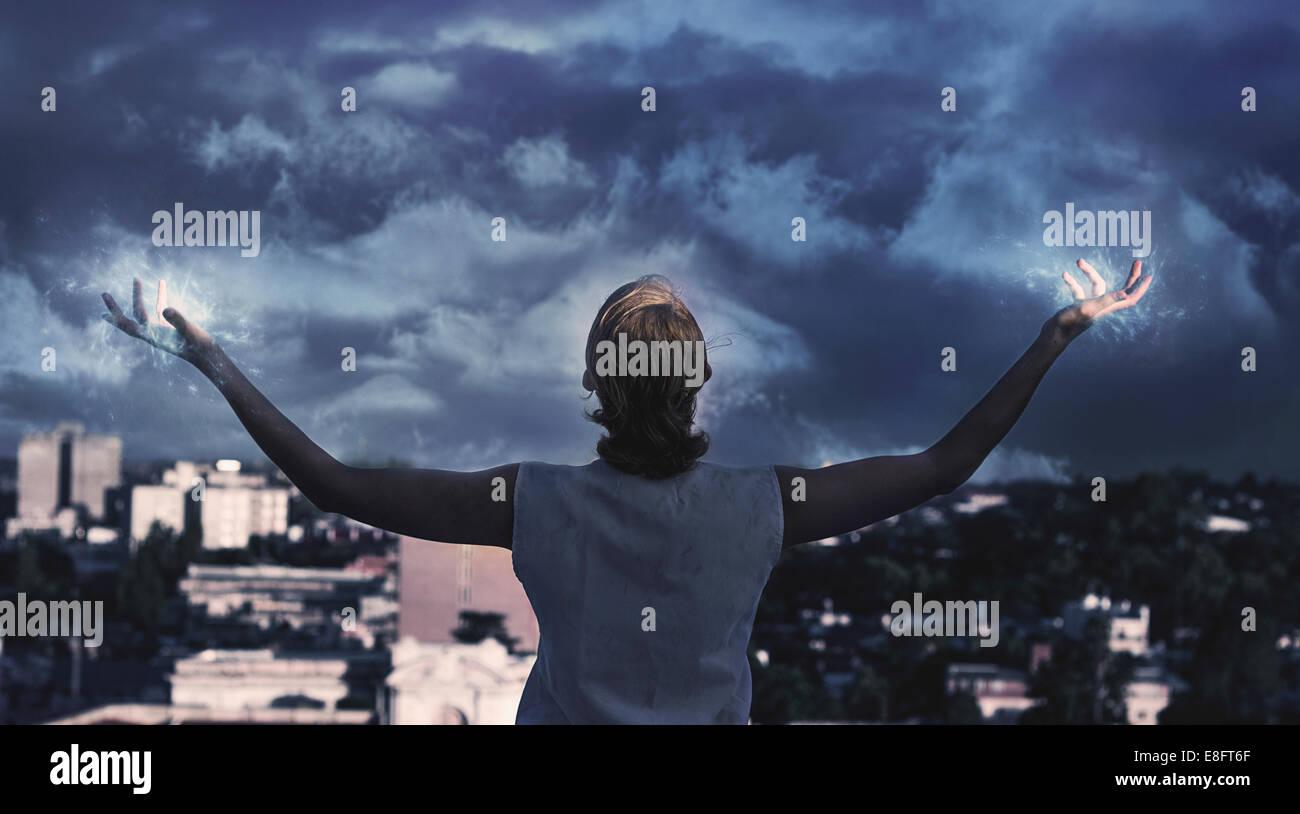 Vista trasera de la niña (10-11) sosteniendo sus brazos al cielo tormentoso Imagen De Stock