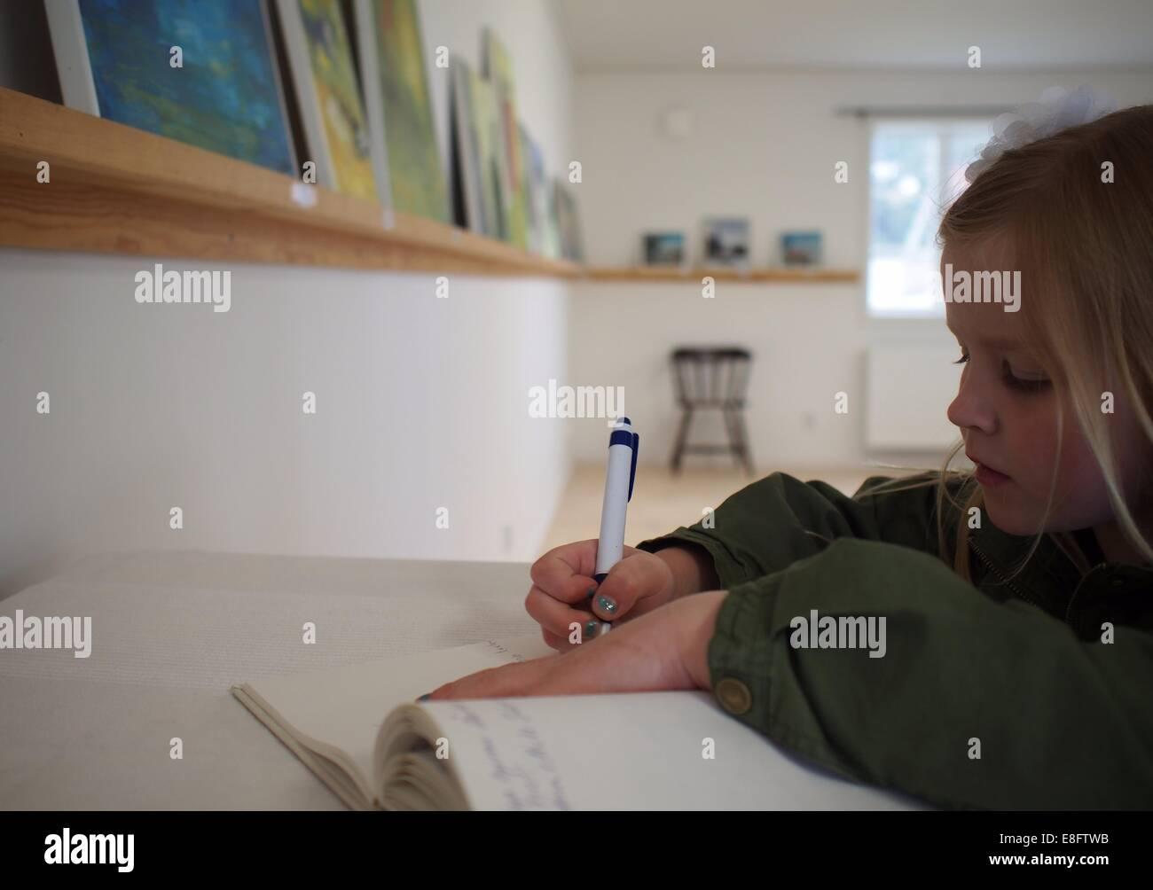 Suecia, Niña (8-9 años) escribe en un libro Imagen De Stock
