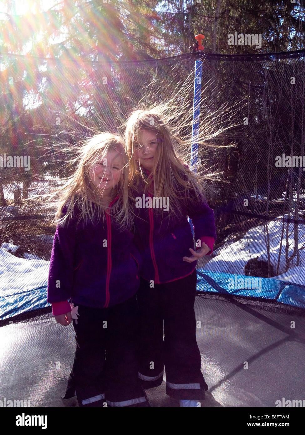 Suecia, dos niñas (6-7 años, 8-9 años) en el trampolín con la electricidad estática del Imagen De Stock
