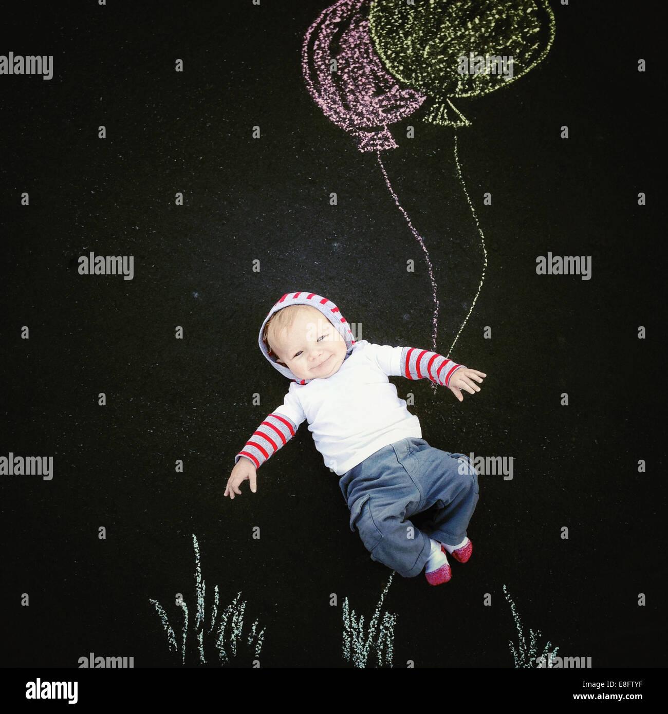 Baby Boy con tiza el dibujo de globos Imagen De Stock