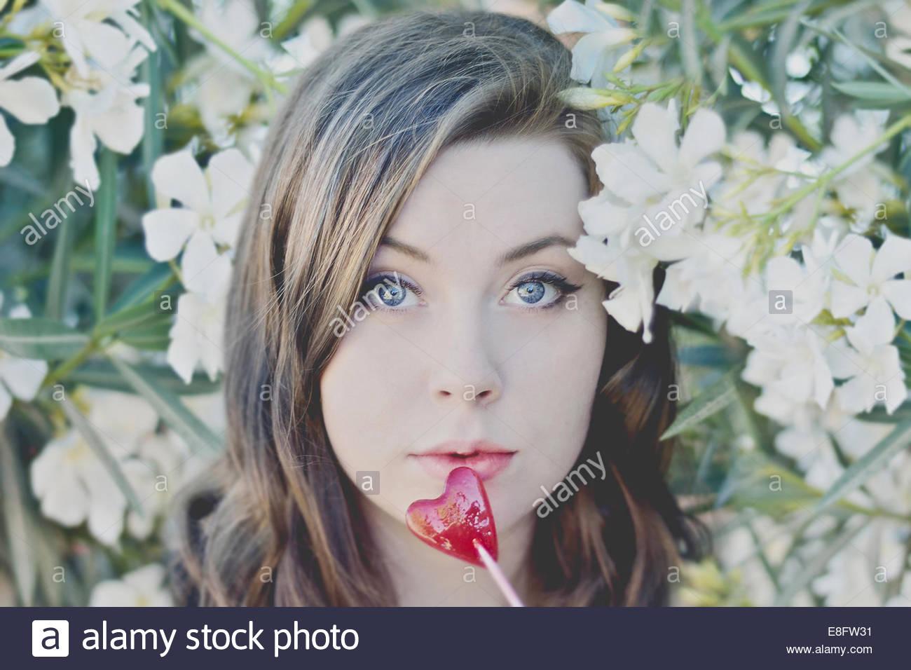 Retrato de mujer con piruleta en forma de corazón y flores en segundo plano. Imagen De Stock