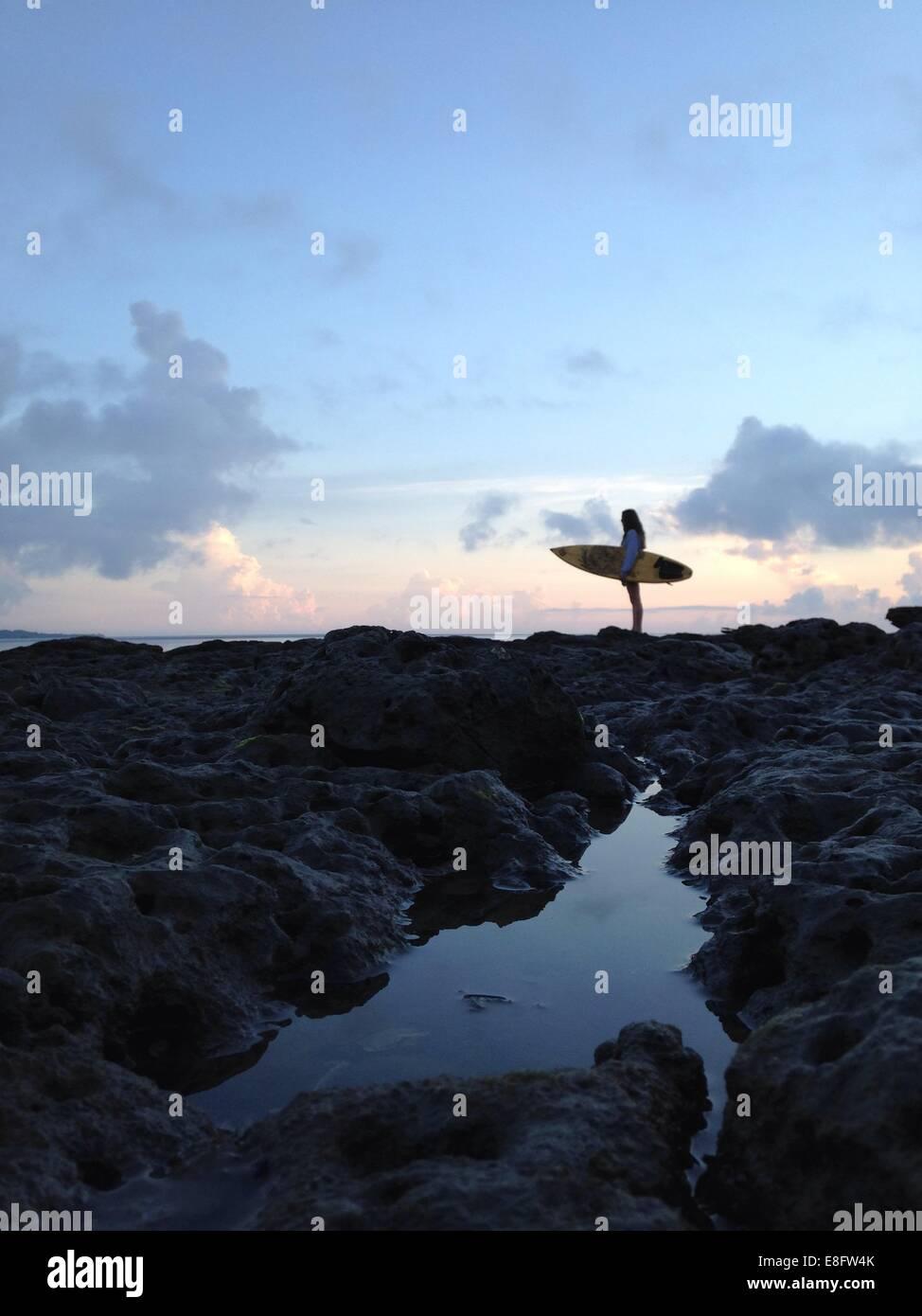 Estados Unidos, la Florida, el condado de Duval, Jacksonville Beach, vista lateral de la mujer sosteniendo las tablas Imagen De Stock
