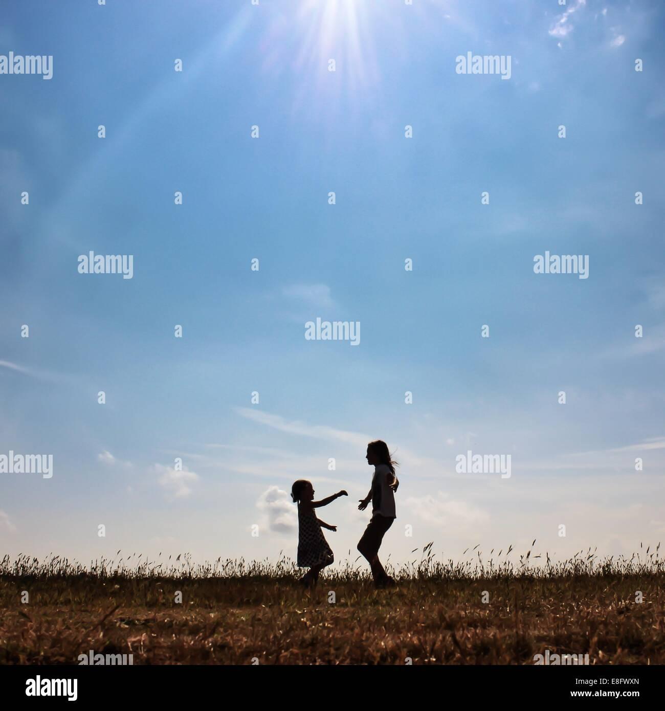 Silueta de dos niñas jugando en una pradera Imagen De Stock