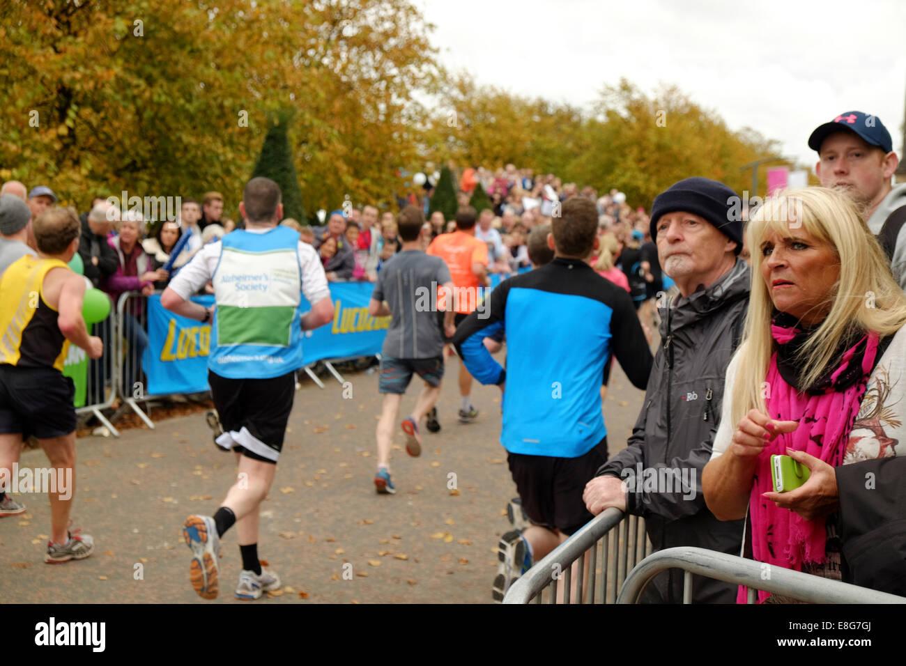 Los espectadores alentar a corredores de maratón acercándose a la línea de meta en Glasgow Green Imagen De Stock
