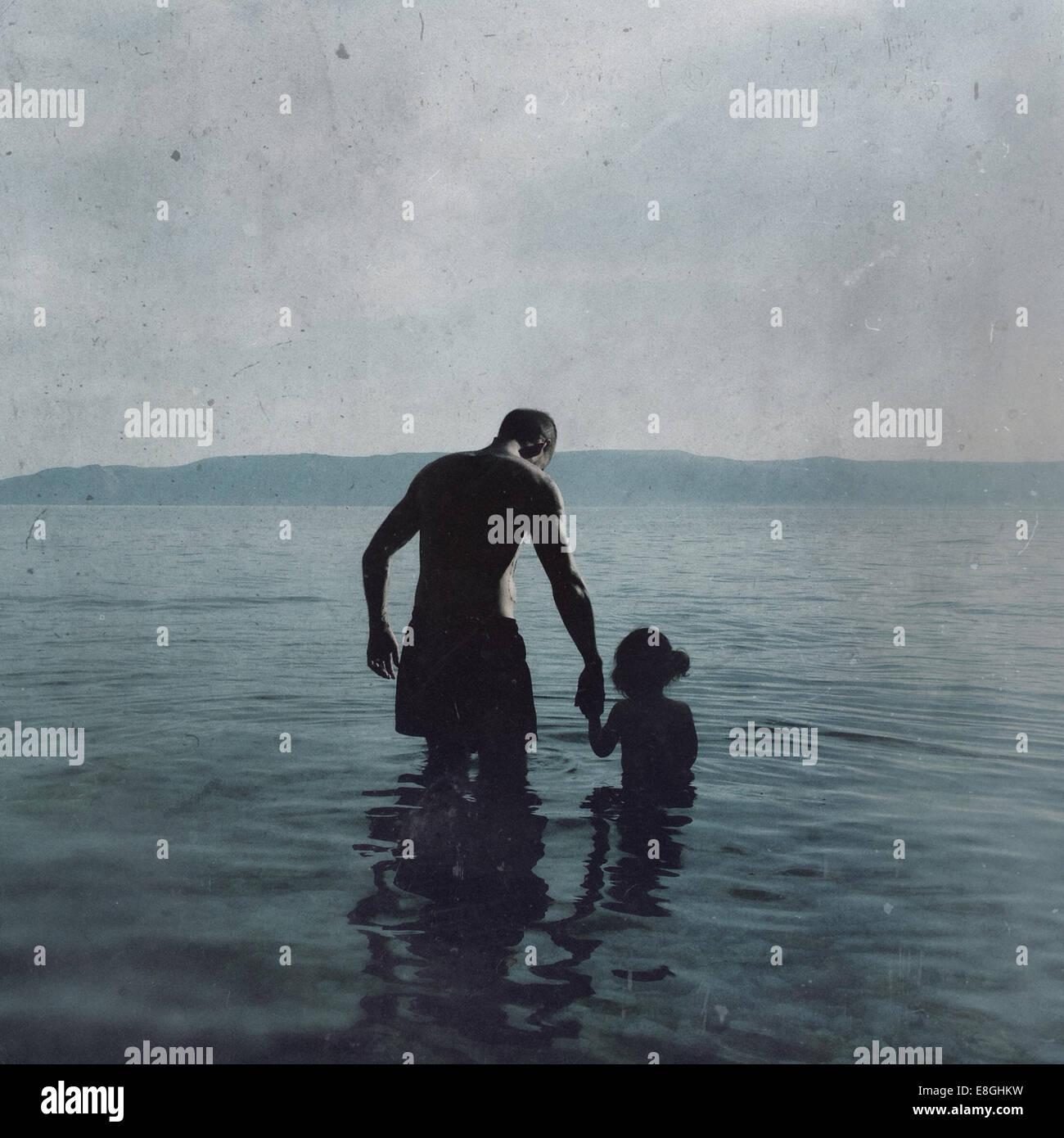 Croacia, padre e hija (2-3) vadeando en el mar Imagen De Stock