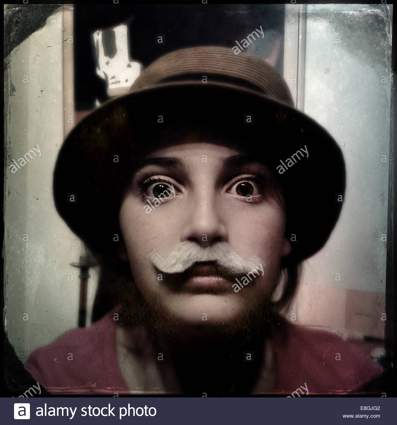 Retrato de una niña con bigote y sombrero Foto de stock