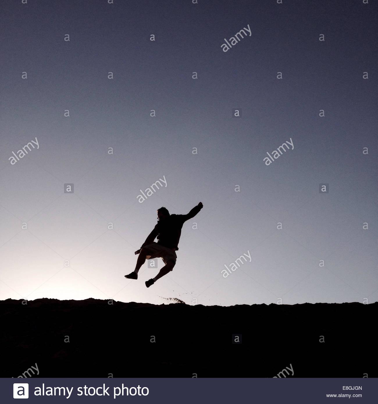 Silueta de hombre saltando en la playa al amanecer Imagen De Stock