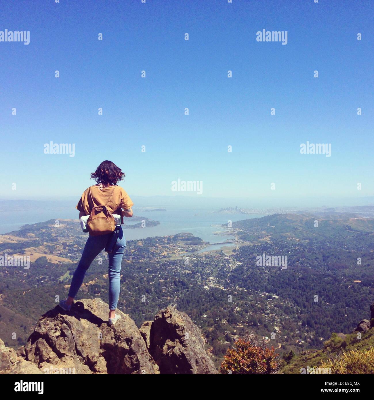 Mujer de pie en el Monte Tamalpais mirando city, San Francisco, California, Estados Unidos, EE.UU. Imagen De Stock