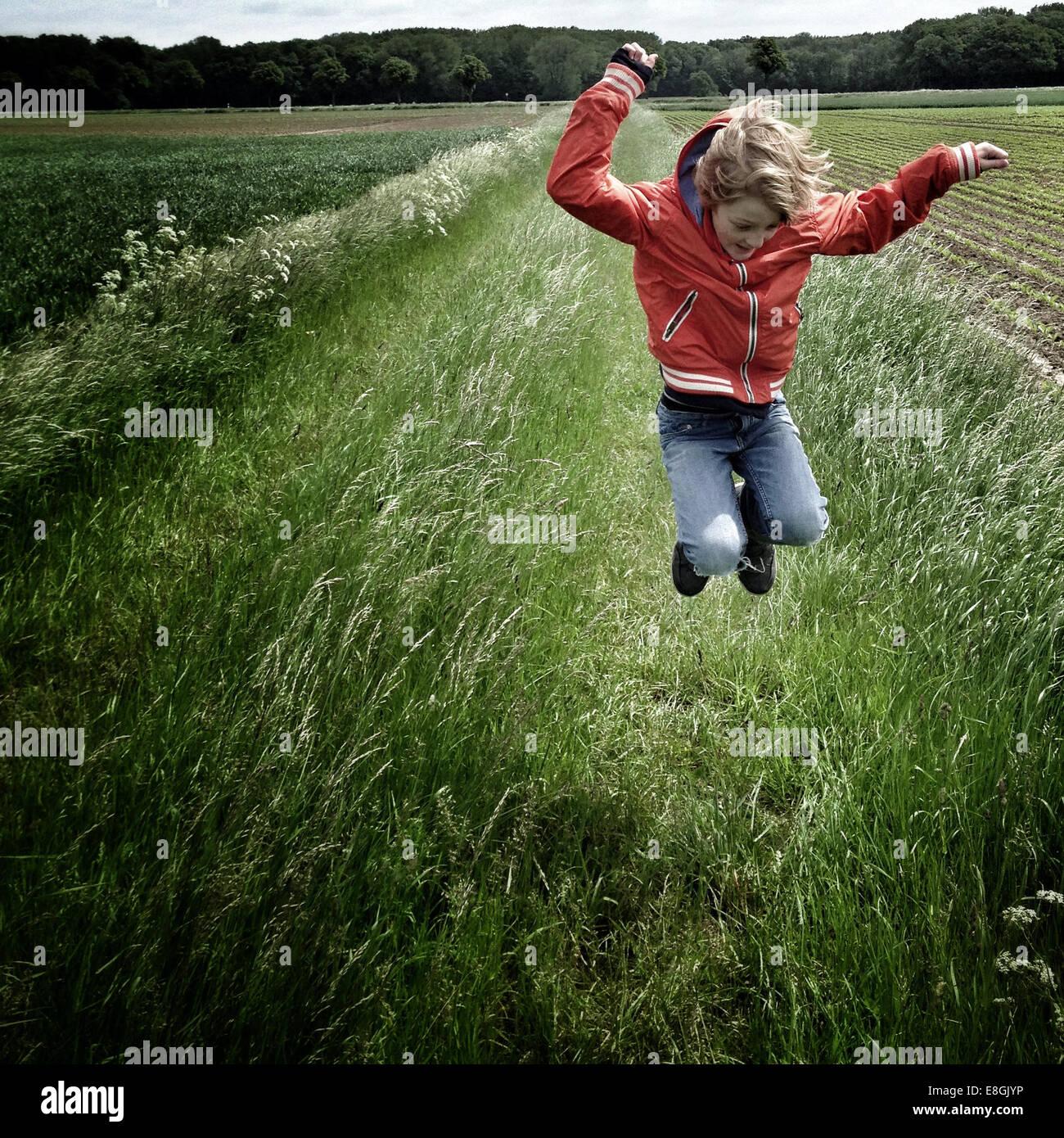 Chico saltando en un campo Imagen De Stock