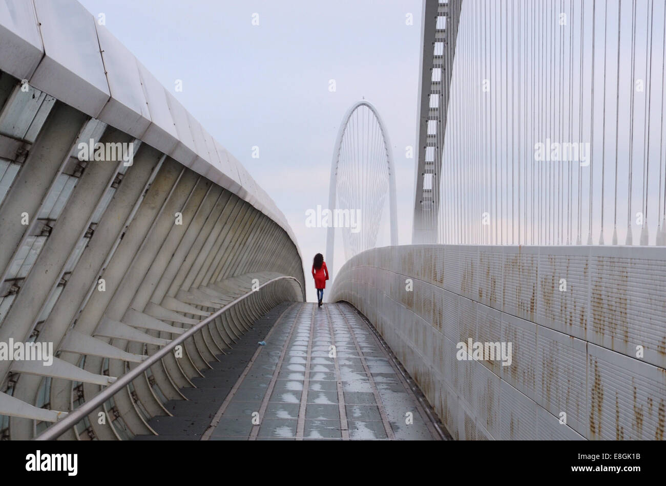 Italia, la mujer en rojo caminando por el puente de Calatrava Imagen De Stock