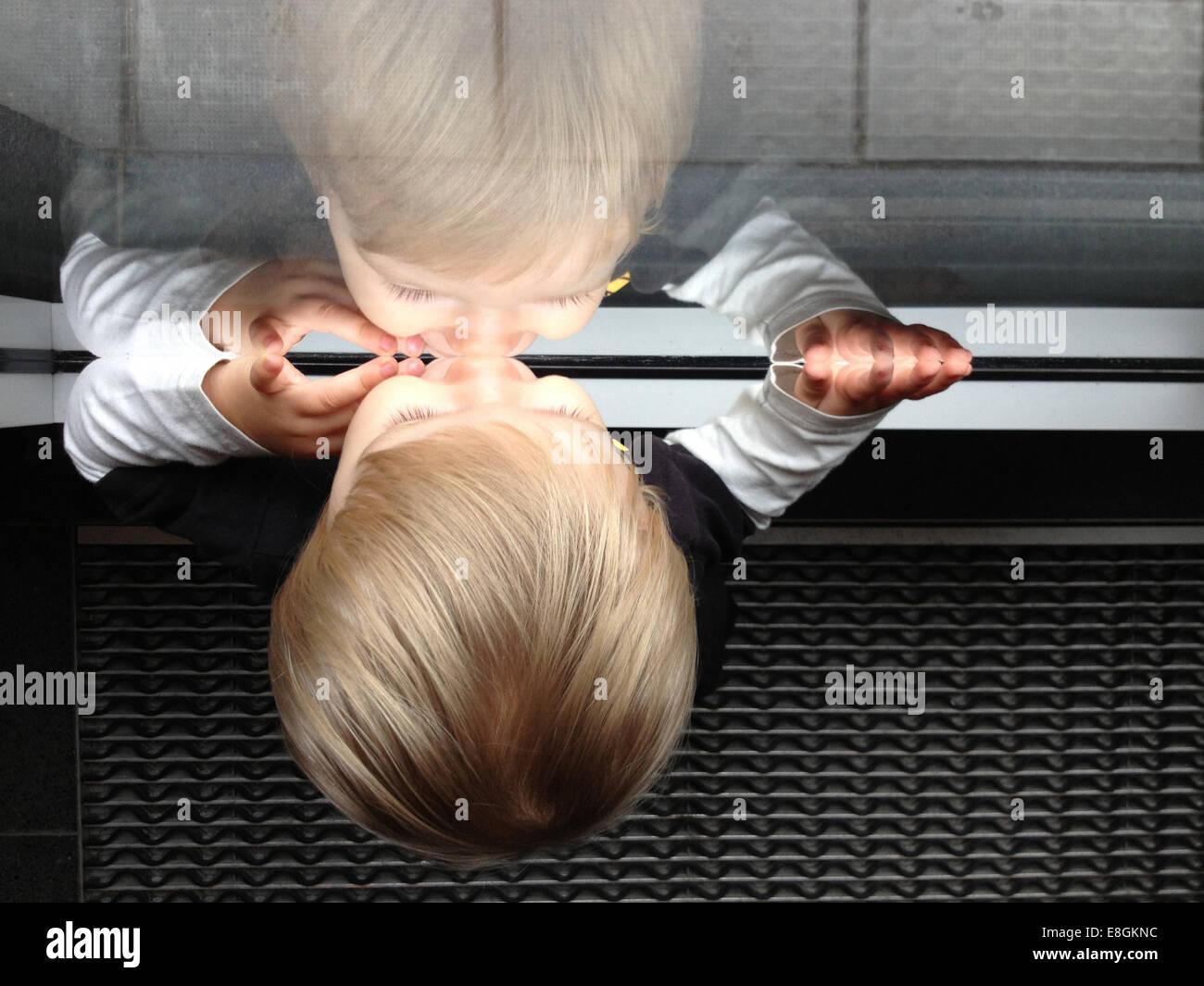Estocolmo, Suecia un poco Chico mirando por una ventana y ver su propio reflejo Imagen De Stock