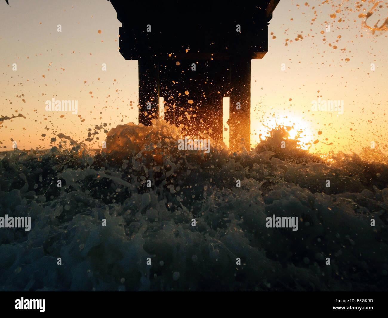 Estados Unidos, la Florida, la playa de San Agustín, amanecer en el muelle con salpicaduras y sun flare Imagen De Stock
