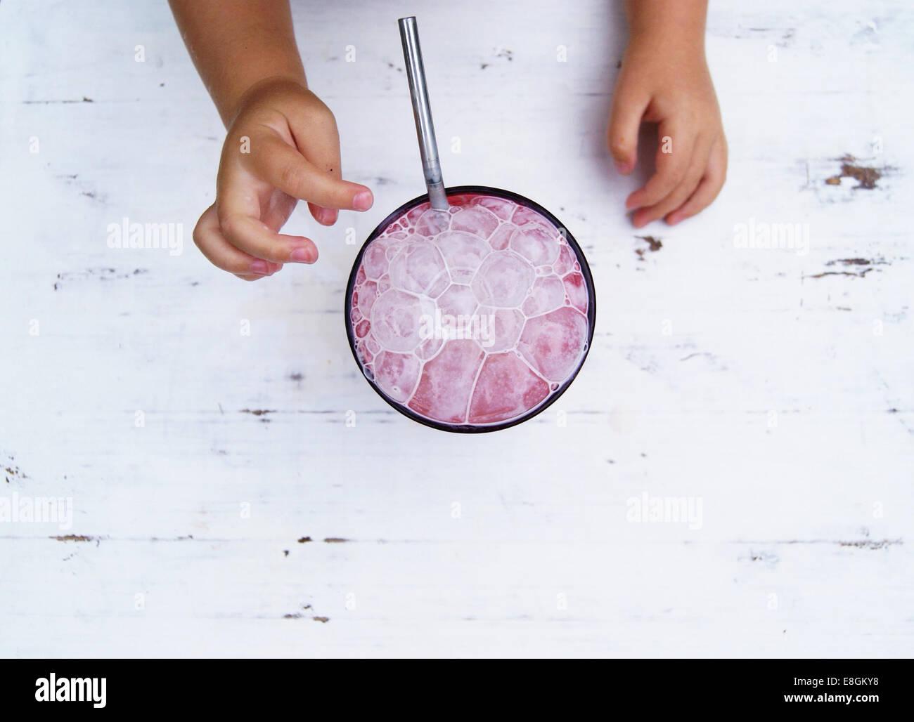 Las manos del niño alcanza para un batido de fresa con burbujas Imagen De Stock
