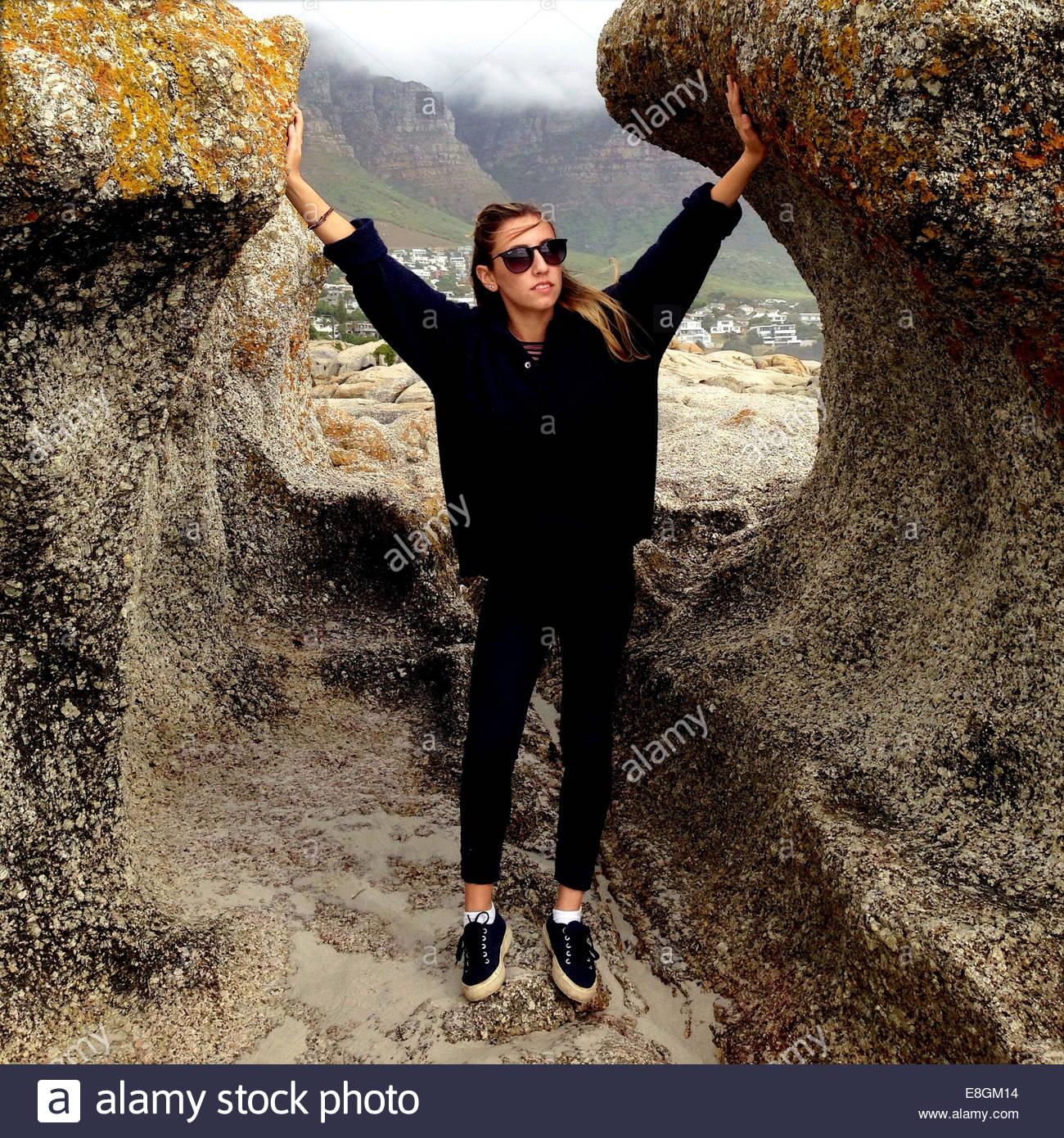 Mujer de pie en la playa entre rocas Imagen De Stock