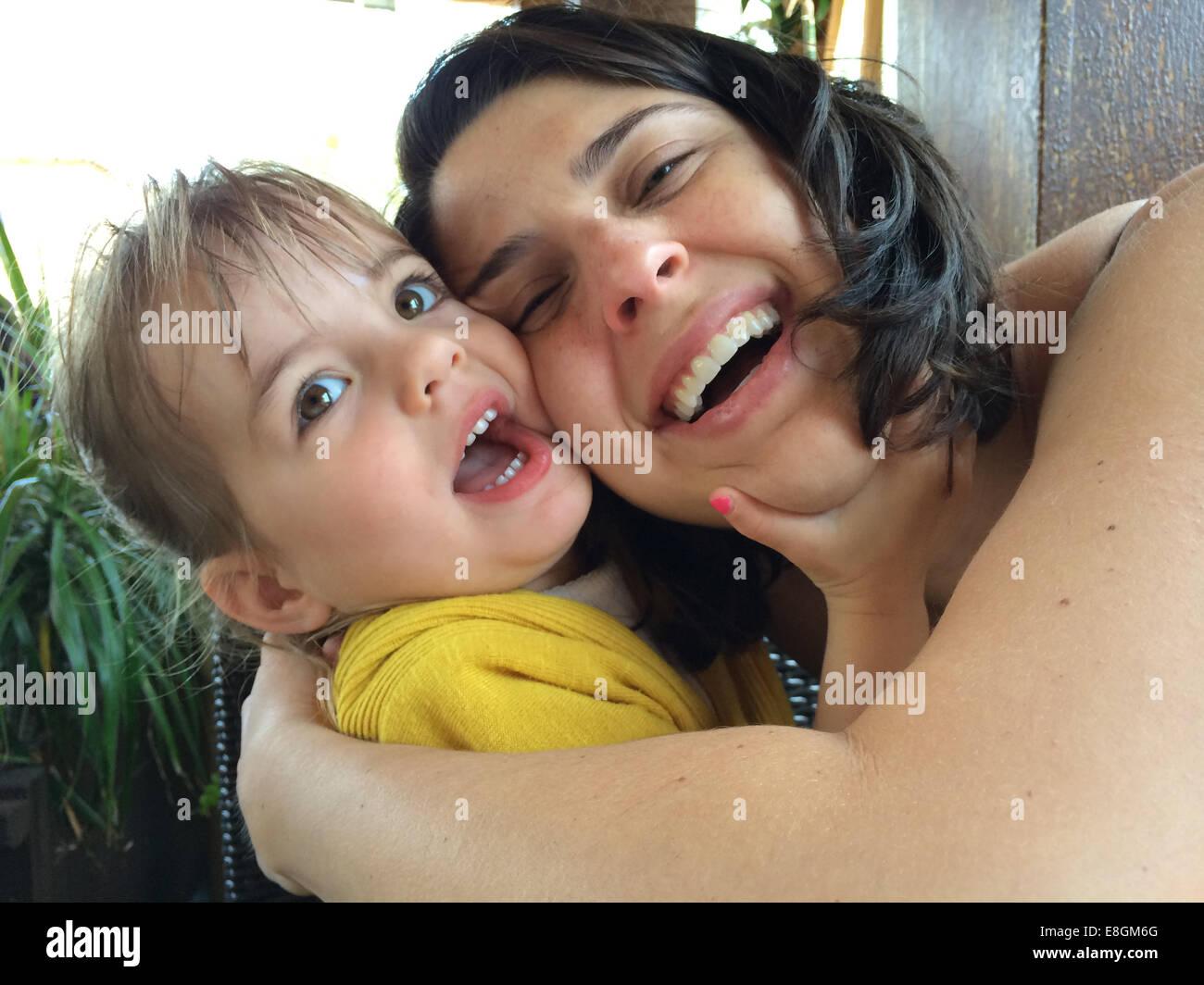 Madre e hija (18-23 meses) abrazar y riendo Foto de stock