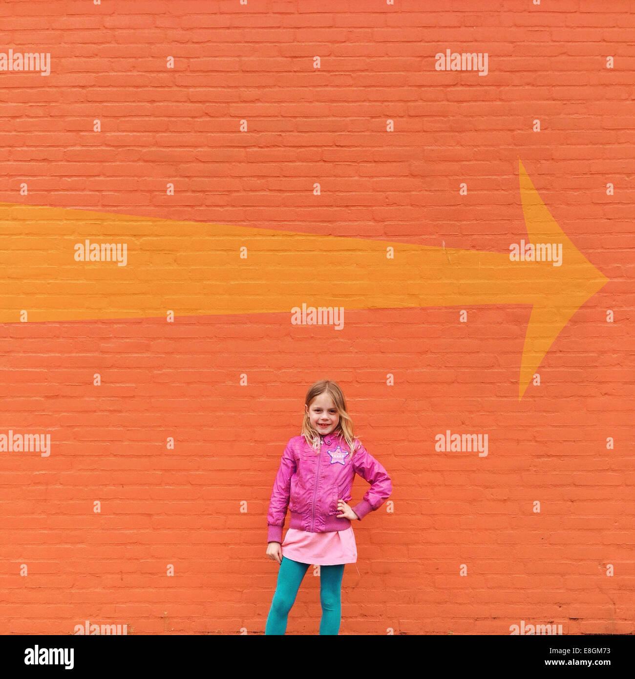 Chica de pie delante de la pared naranja y una flecha direccional Foto de stock