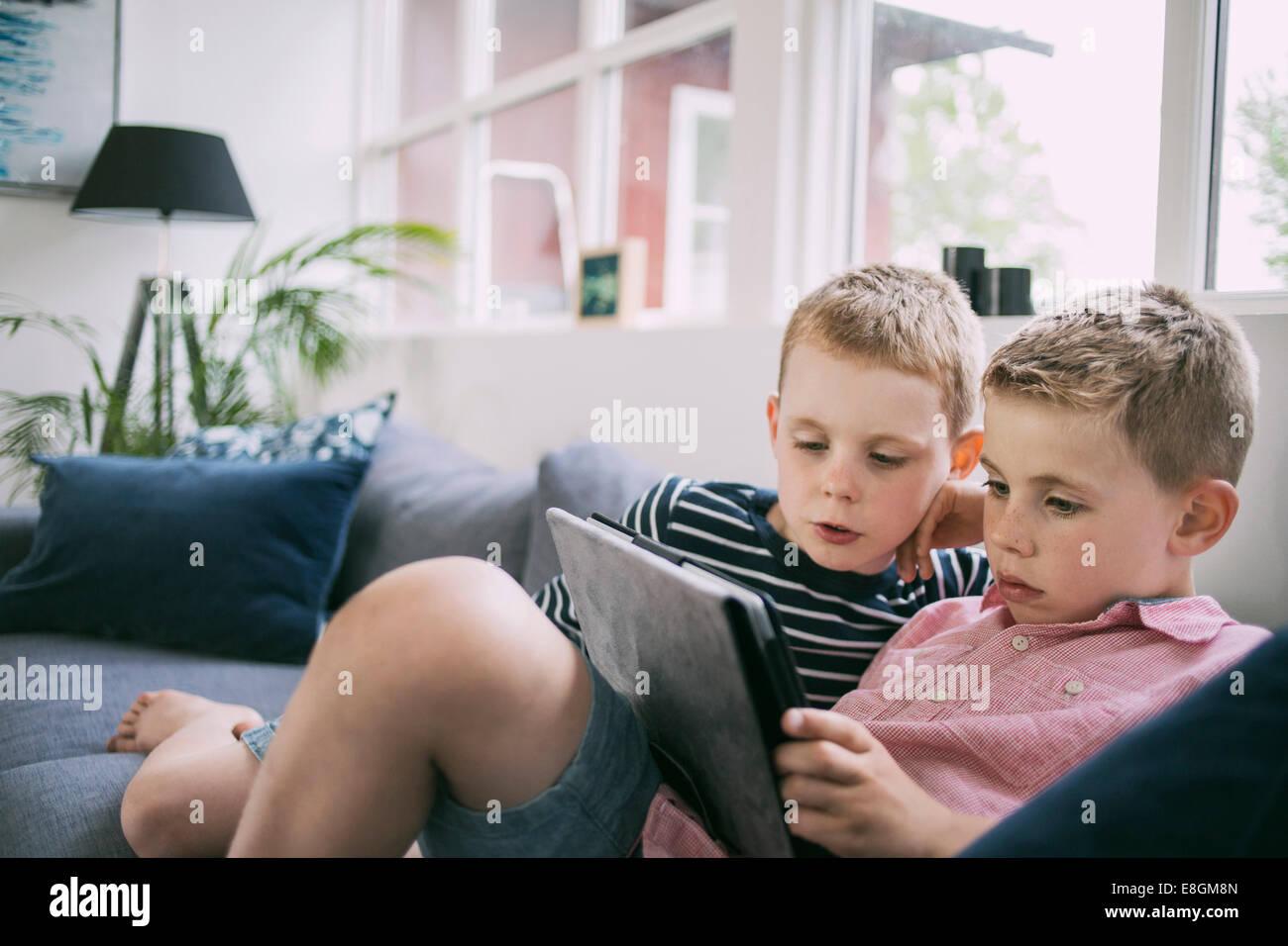 Hermanos utilizando tablet digital en el sofá en casa Imagen De Stock
