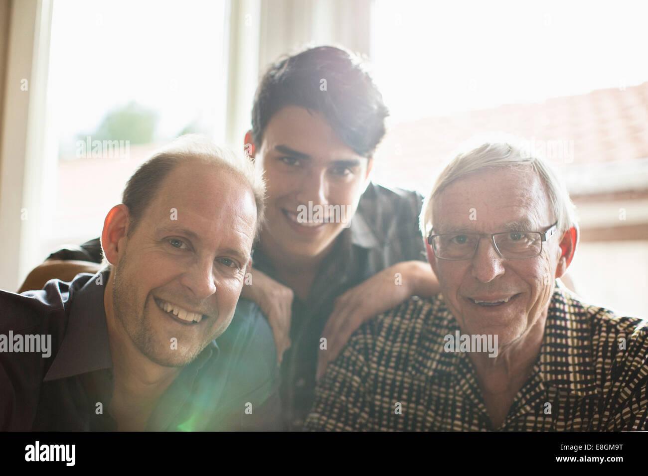 Retrato de tres generaciones de la familia juntos en casa sonriente Foto de stock