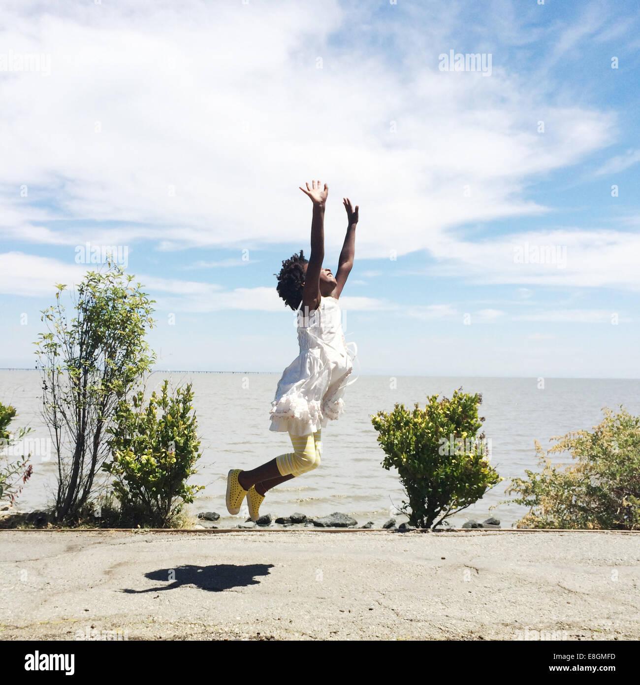 Chica saltar en el aire en la playa Imagen De Stock