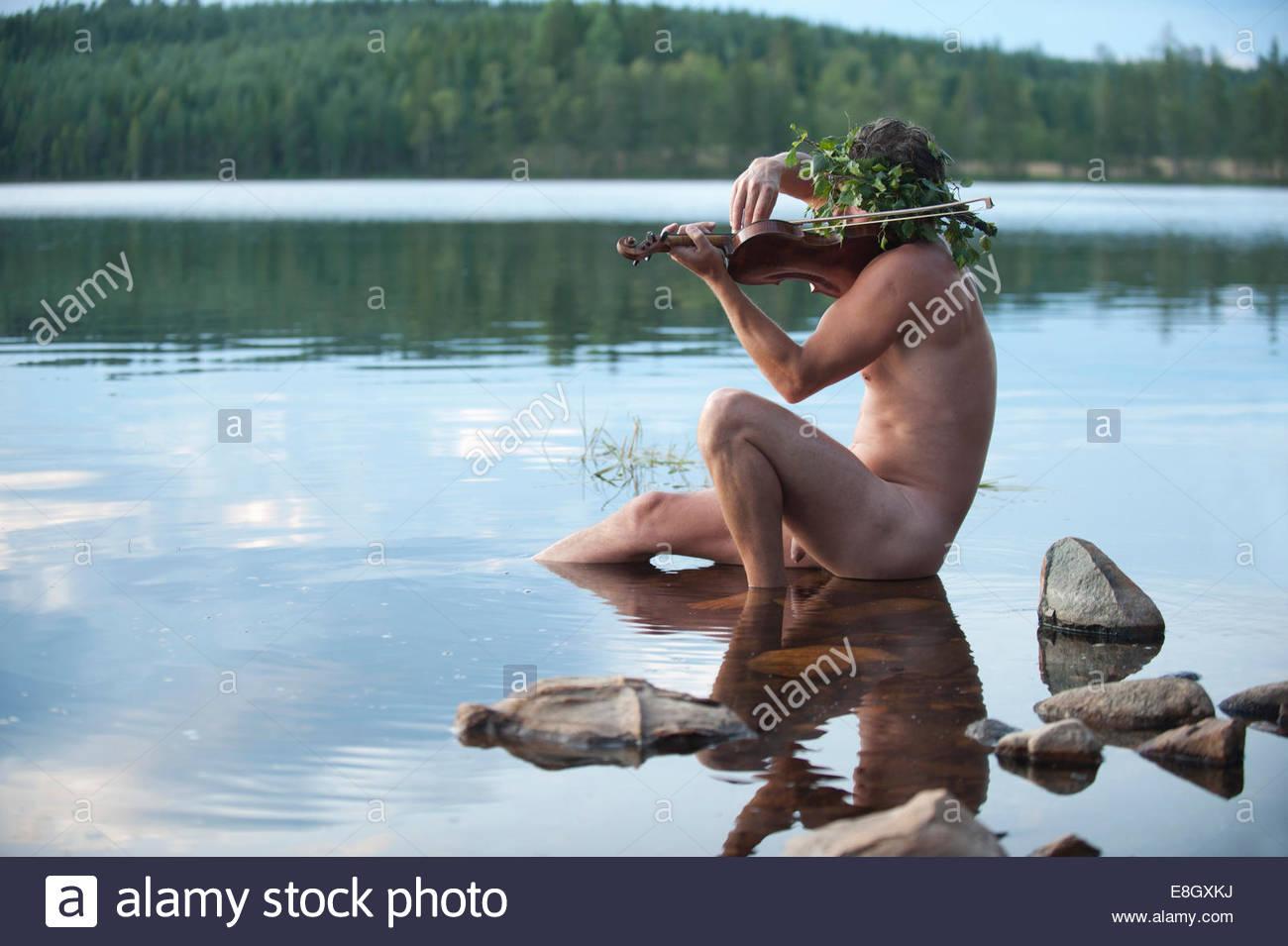 Vista lateral del espíritu del agua a tocar el violín en el lago Foto de stock