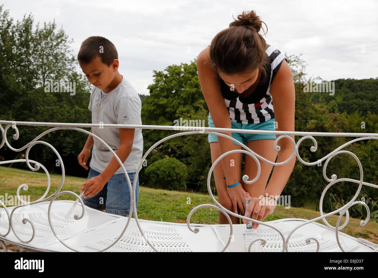 Niños pintando muebles de hierro Foto de stock