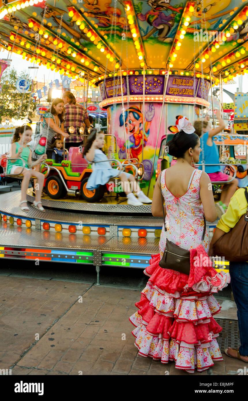 Mujer española en el tradicional vestido de fiesta esperando junto a chlidrens Carrusel tiovivo de feria anual. Foto de stock