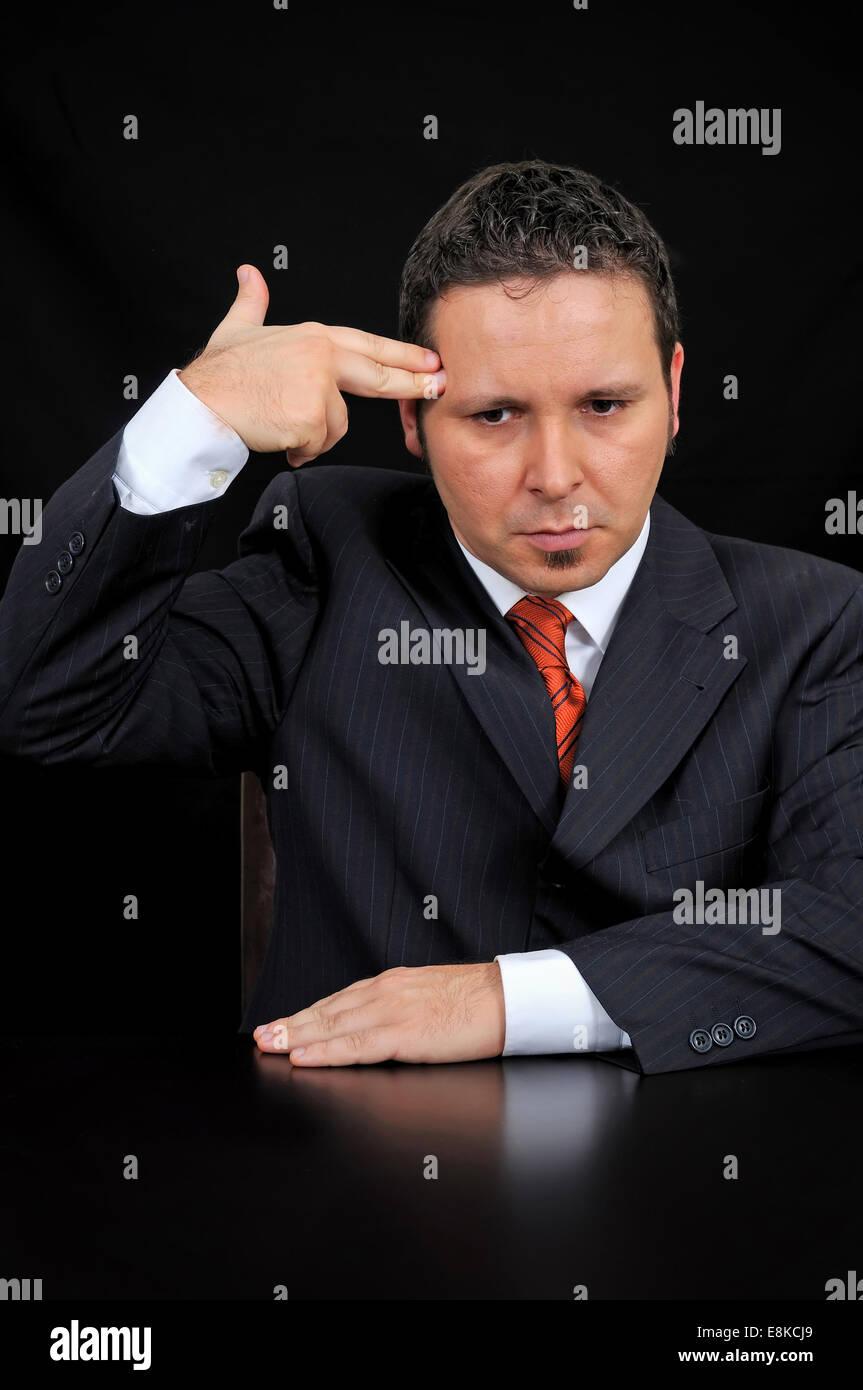 Joven Empresario sosteniendo la mano a su cabeza, simulando una pistola. Imagen De Stock