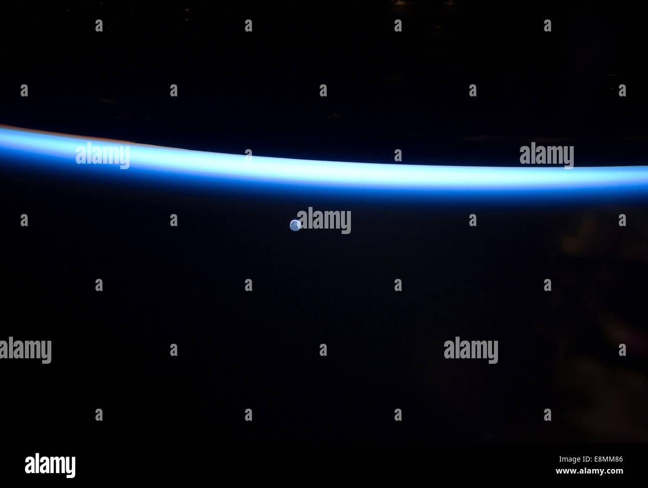 Marzo 6, 2011 - Earth la delgada línea de la atmósfera y una menguante Luna. Imagen De Stock