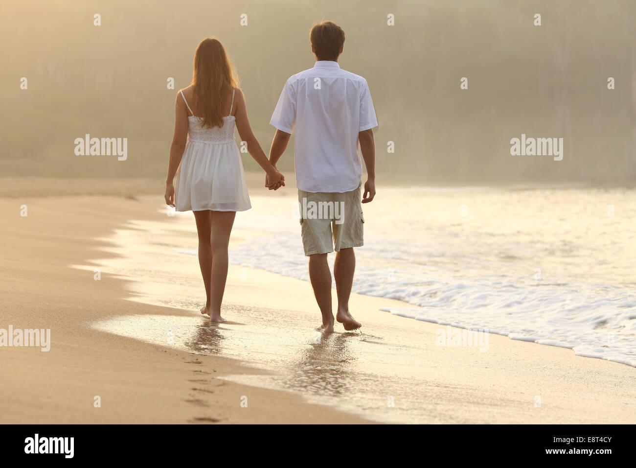 Vista posterior de una pareja caminando y tomados de la mano en la arena de una playa en el atardecer. Foto de stock