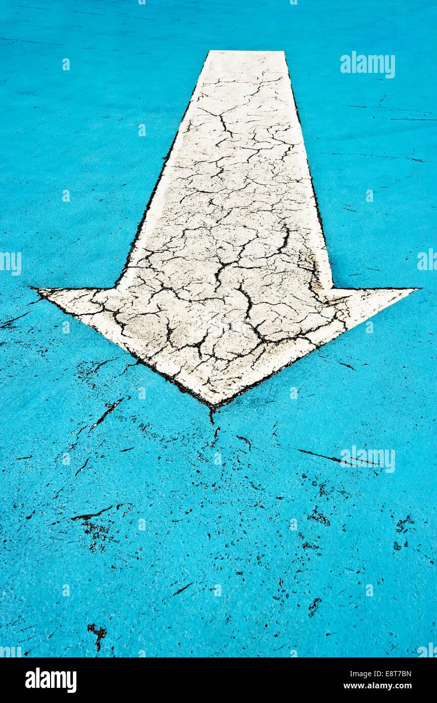 Flecha blanca sobre azul de hormigón con grietas Imagen De Stock