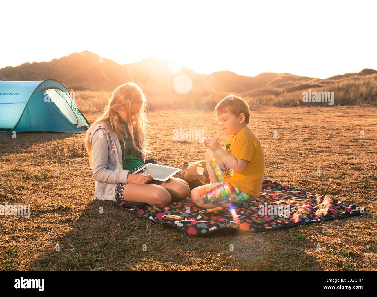 Los niños acampar en manta para picnic con ipad en verano. Hermano y hermana camp holiday en UK Inglaterra Imagen De Stock