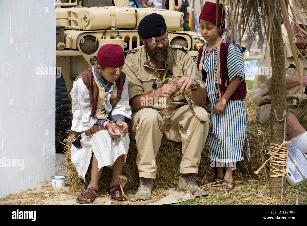 Soldado haciendo un muñeco de láminas con niños vestidos tradicionalmente viendo en el acuartelamiento Imagen De Stock